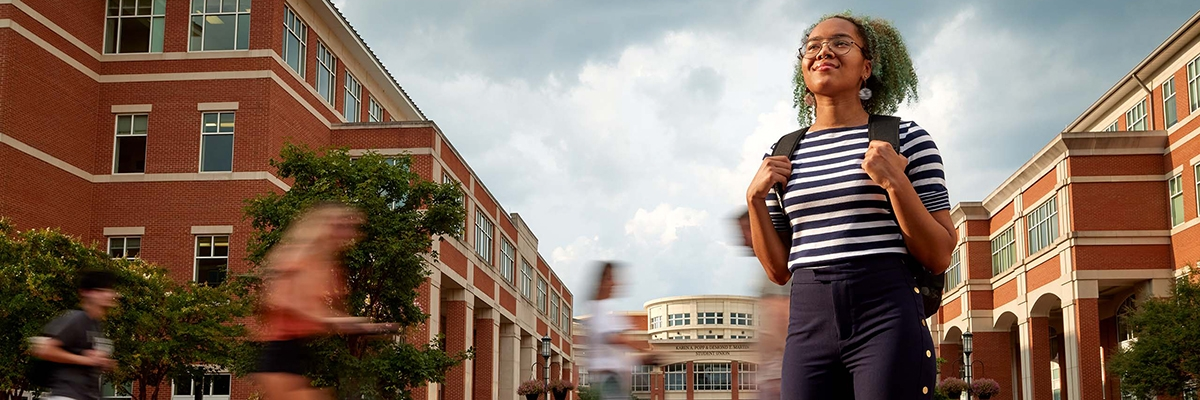 UNC Charlotte student with blurred images of walking students behind her