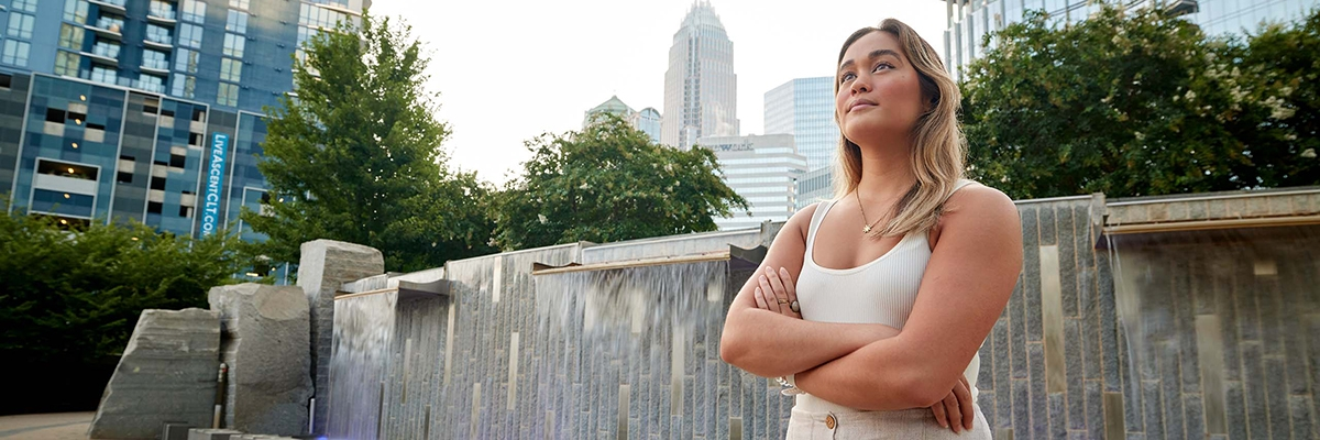 UNC Charlotte student in front of fountain in uptown Charlotte